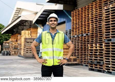 Portrait Of Young Indian Worker Working In Logistic Industry Outdoor In Front Of Factory Warehouse.