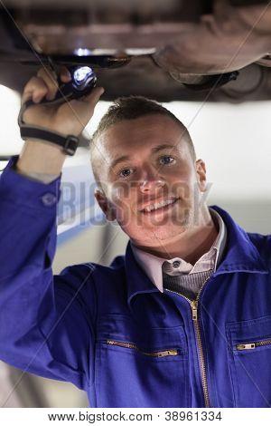 Mechanic illuminating the below of a car in a garage