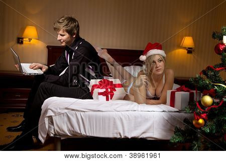 Young woman in Santa's hats  with glass of champagne lying on bed remain all alone because her boyfriend  is busy with laptop and ignore her