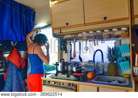 Woman Inside Caravan Rv, Looking Outside From Kitchen Area. Cooking In Campervan. Holidays, Adventur