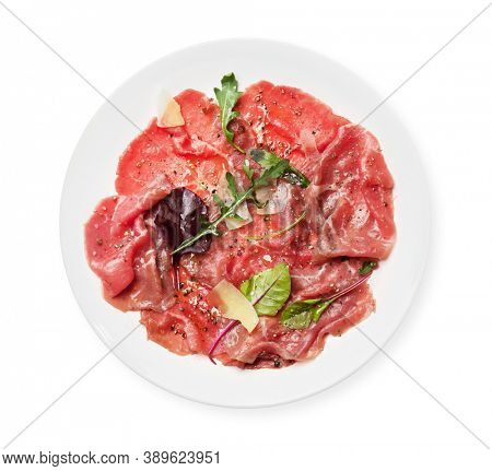 Marbled beef carpaccio with arugula, spices and parmesan cheese. Top view flat lay isolated on white