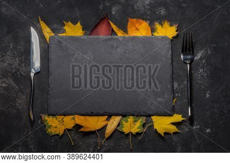 Autumn Layout With Still Life Of Black Stone Tray, Autumn Leaves, Fork And Knife. Autumn, Top View.