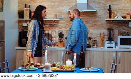 Young Man Flirting During Romantic Date With Woman, At Home, In The Kitchen During Dinner. Frustated