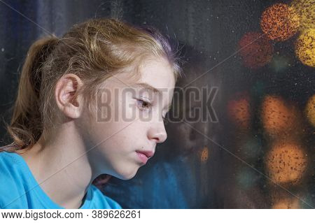 A Brown Eyed Girl In Blue Shirt On The Window Sill Against A Foggy Window With Blurred Night Backgro