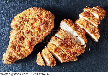 Fried Breaded Chicken Breasts, A Whole One And A Sliced One On A Black Stone Plate, Horizontal View