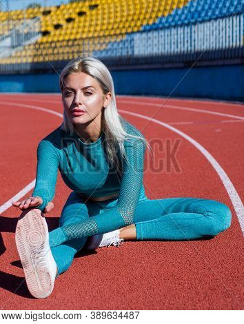 Sportive Woman Stretch. Healthy Dieting. Flexible Woman On Stadium Gym. Female Trainer Do Stretching