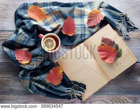 Autumn Leaves, Cup Of Black Tea With Lemon Slice, Warm Scarf And Notebook On Wooden Table. Fall Seas