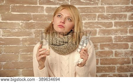 Laid Up With A Bad Cold. Medication And Increased Fluid Intake. Unhealthy Woman Holding Pills And Wa