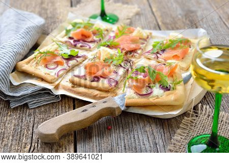 Tarte Flambee From Alsace With Smoked Salmon And Rocket Leaves Served With Local Alsatian White Wine