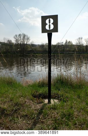 Sign Number Eight On The River Bank.  Mooring Number With Mooring Ball.