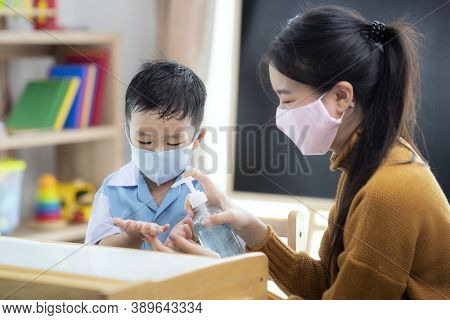 Asian Woman Teacher Use Alcohol Gel On Hand Of Her Student For Prevent Virus From Covid19 In Classro