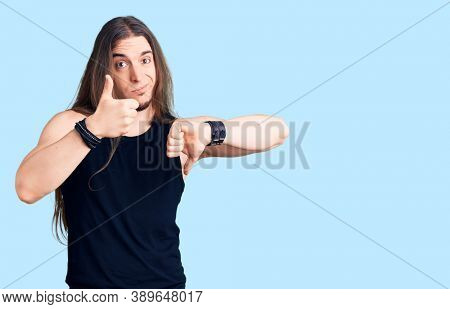 Young adult man with long hair wearing goth style with black clothes doing thumbs up and down, disagreement and agreement expression. crazy conflict
