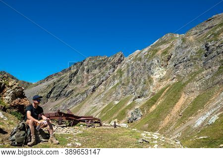 Hiker Man Resting And Drinking Water In The Mountain
