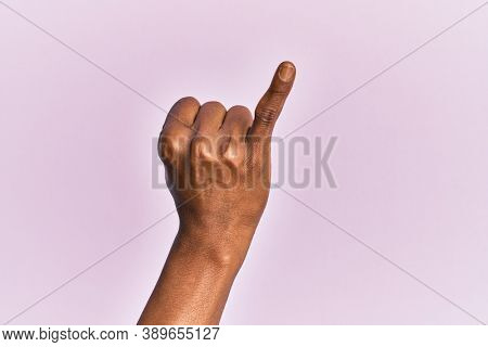 Arm and hand of black middle age woman over pink isolated background showing little finger as pinky promise commitment, number one