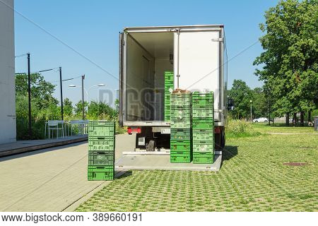 Unloading Food Crates From A Van. Delivery Of Goods To Shops And Cafes