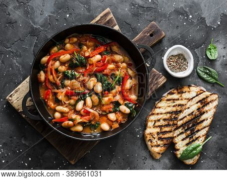 Greek Style Tomato Sauce, Spinach, Paprika, Beans Stew In A Cast Iron Pan On A Rustic Board On A Dar