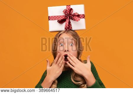 Charming Blonde Girl 12-14 Years Old In Warm Green Sweater Hold Gift Box With Red Ribbon On Her Head