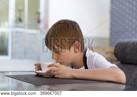 Boy Is Drinking Tea In Cafe. Child Drinks Coffee From White Mug.