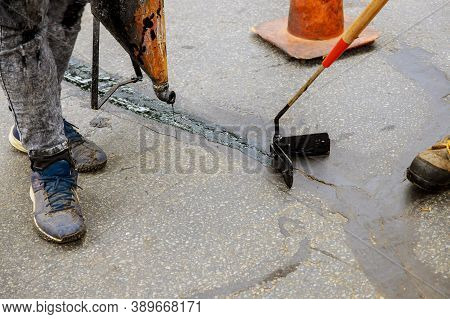 Road Surface Restoration Work In The Worker Performs Road Patcher Work Repair Of Cracks By Filling A