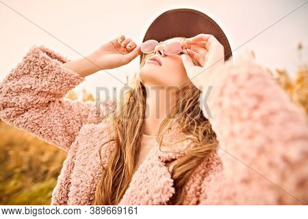 Autumn fashion. Stylish young woman in a fashionable fur coat and hat looks at the sky through pink glasses in an autumn park.
