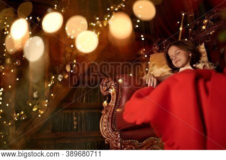 Magic for Christmas. Cute little girl fell asleep in a cozy armchair by the New Year tree, surrounded by lights. Christmas Eve.