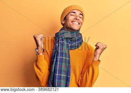 Young african amercian man wearing casual winter clothes very happy and excited doing winner gesture with arms raised, smiling and screaming for success. celebration concept.