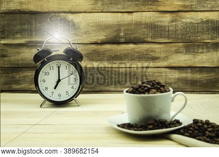 Clock Showing Seven O'clock In The Morning. Clock And Coffee Grains As Background. The Concept Of Wa
