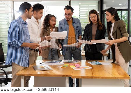 Interracial asian business team brainstorming idea talk and discuss at office meeting room after reopen due to coronavirus COVID-19 city lockdown. Business startup meeting and brainstorm concept.