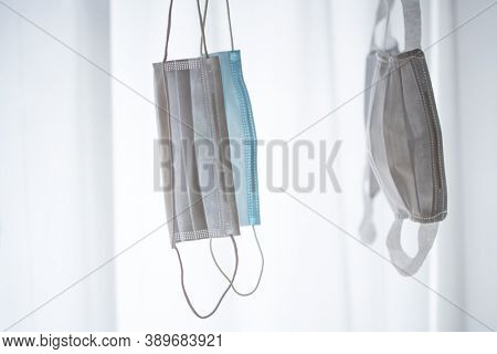 Reusing used masks. Masks hanging from a laundry clip hanger or a drying rack, while drying and disindfection under sunlight.