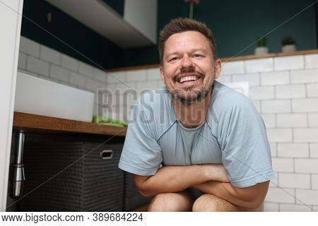 Man With Blissful Smile Sits On Toilet. Constipation In A Man What To Do At Home Concept