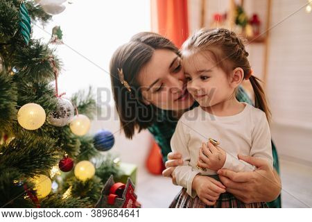 Happy Family Mom And Daughter On A Christmas Winter Sunny Morning In A Decorated Christmas Celebrati