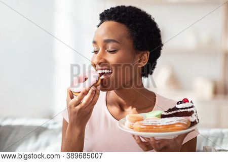 Diet Breakdown, Cheat Meal And Imbalanced Nutrition Concept. Beautiful Young Black Woman With Plate