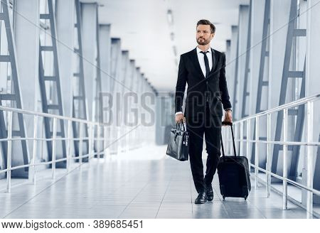 Middle-aged Handsome Businessman Walking By Airport Terminal With Luggage And Case, Looking At Copy