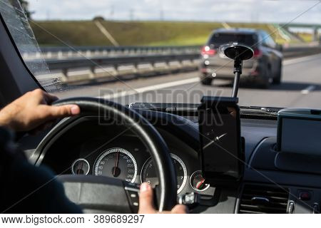 Driver's Hand On The Steering Wheel Of Driving Car With Smartphone On Panel