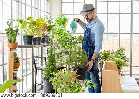 An Elderly Man With Glasses Enjoys Caring For His Plants, Watering, Spraying, And Decorating The Pla