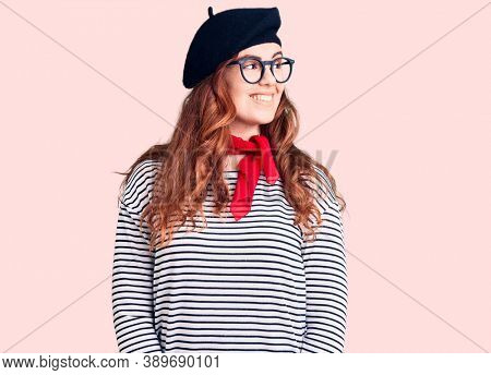 Young beautiful woman wearing french look with beret looking away to side with smile on face, natural expression. laughing confident.