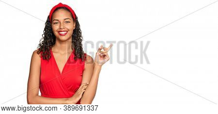 Young african american girl wearing elegant and sexy look with a big smile on face, pointing with hand and finger to the side looking at the camera.