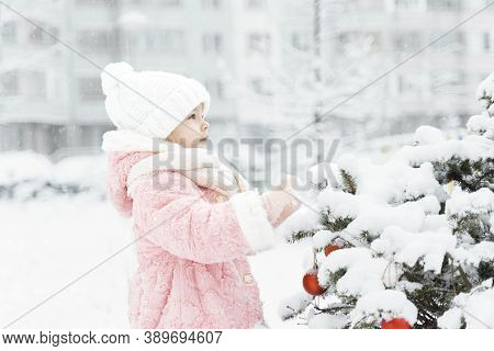 A Cute Little Girl In A Pink Fur Coat Decorates A Christmas Tree In The Yard. Everything Is Covered