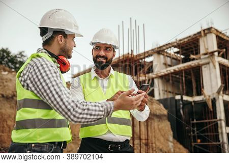 Men In Waistcoats And Hardhats Smiling And Looking At Each Other While Browsing Smartphone During Br