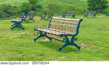 Empty Park Bench On Green Grass Lawn In Lush Parkland In Summer