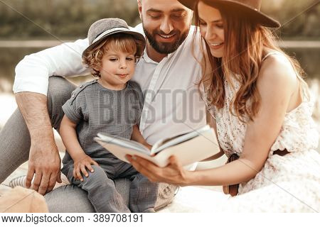 Cheerful Parents Reading Book To Cute Son While Resting On Coast Of Pond On Summer Day