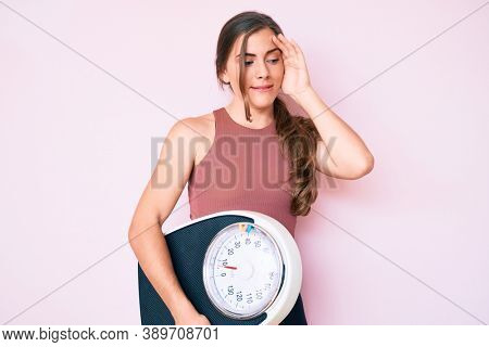 Beautiful young caucasian woman holding weight machine to balance weight loss stressed and frustrated with hand on head, surprised and angry face