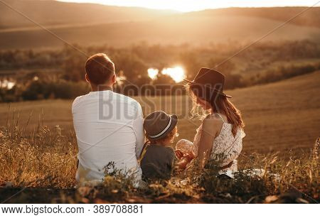 Back View Of Anonymous Parents And Kid Sitting On Blanket And Resting During Picnic At Sundown In Na