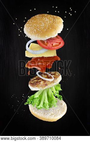 Levitating Cheeseburger Ingredients On Dark Background. Burger Components Floating In The Air: Chees
