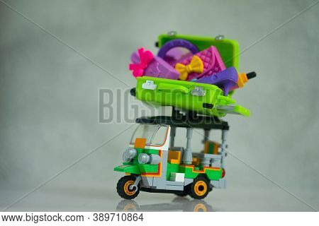 Miniature Green Suitcase And Women Accessories Inside On Top Tuk Tuk Car. Concept Of Travel And Shop