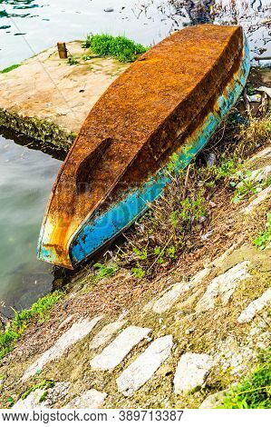 Old And Rusty Iron Overturned Boat On The Shore, On The Edge Of A River.