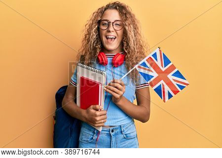 Beautiful caucasian teenager girl exchange student holding uk flag smiling and laughing hard out loud because funny crazy joke.