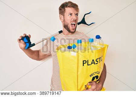 Young caucasian man holding recycling bag with plastic bottles and waste picker angry and mad screaming frustrated and furious, shouting with anger. rage and aggressive concept.