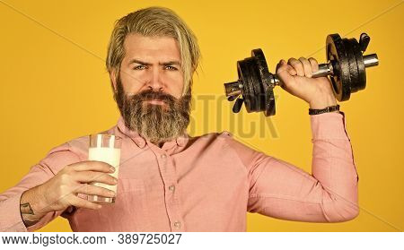 Vitamins For Muscles. Sportsman Hold Dumbbell And Glass Of Milk. Protein Diet. Protein Cocktail. Sou