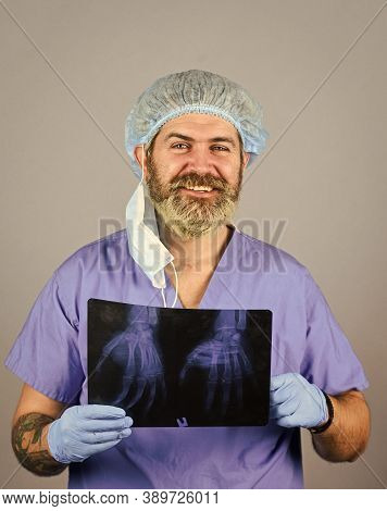 Doctor Holds Pictures Of Bones. Fracture And Bone Damage. Doctor Examines Radiographic Snapshot Of W